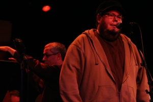 Shane Koyczan (sans book) with Sal Ferreras conducting in the background